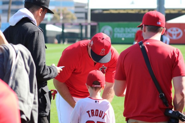 Angels superstar Mike Trout signs a ball for a young fan.